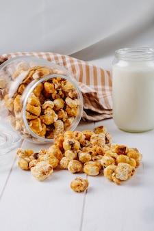 La vista laterale del popcorn al caramello dolce ha sparso da un barattolo di vetro sulla tavola bianca