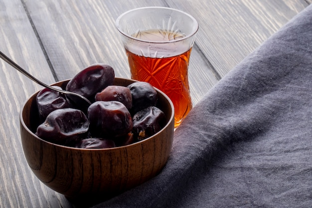 Side view of sweet dried date fruit in a bowl with armudu glass of tea on a wooden rustic