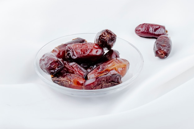 La vista laterale del dattero secco dolce fruttifica in un piattino su fondo bianco