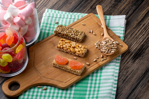 Side view of sweet kozinaki of sunflower seeds sesame and peanuts on a wooden board and with marmalade candies in glass jar on rustic