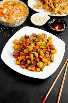 Side view of sweet and sour duck with vegetables and pepper on plate