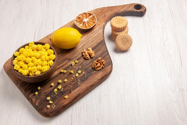 Side view sweets appetizing cookies and bowl of candies nuts and lemon on the cutting board on the white table