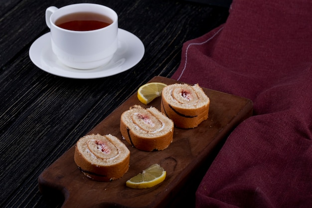 Side view of swiss roll slices with raspberry jam on a wooden board served with a cup of tea