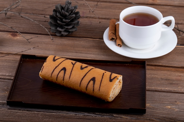 Side view of swiss roll with apricot jam on a wooden board served with a cup of tea on rustic background