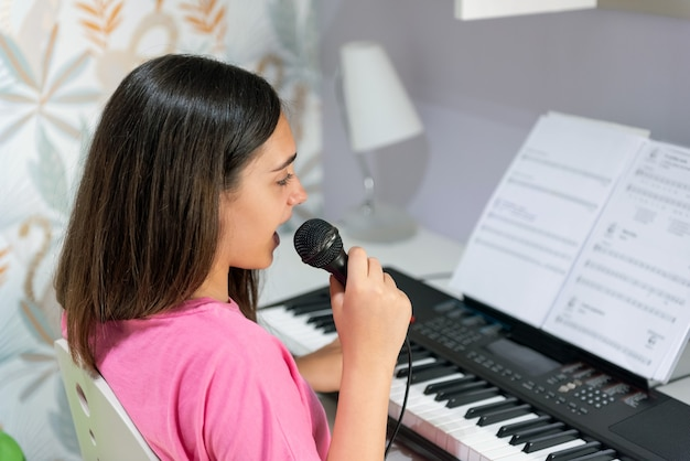 Side view of talented teen girl with microphone performing song and playing electric piano during free time at home