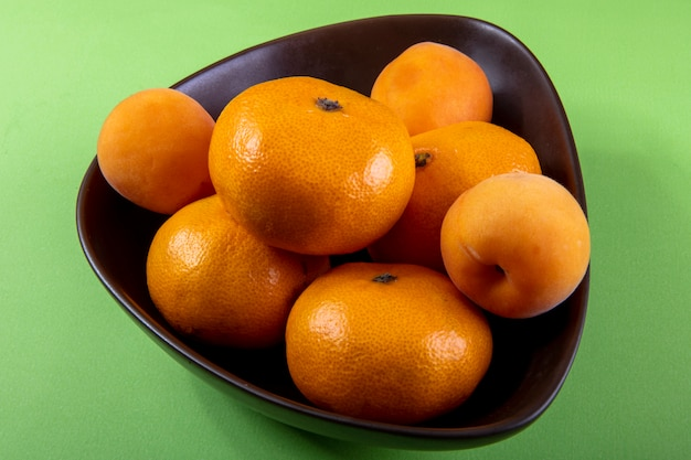 Side view tangerines in a bowl on light green