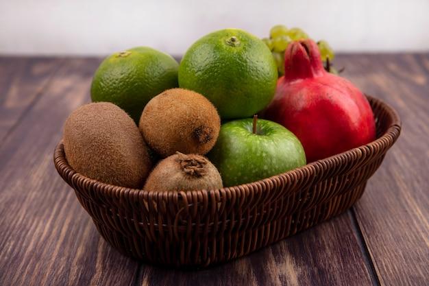 木製の壁のバスケットにキウイリンゴとザクロの側面図みかん