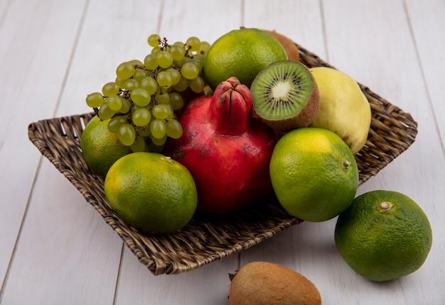 白い壁のバスケットにザクロ梨リンゴブドウとキウイの側面図みかん