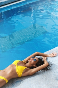 Side view of tanned woman in yellow bikini and sunglasses lying down on a summer day near poolside.