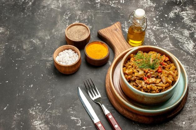 Vista laterale piatto gustoso piatto gustoso sul tabellone accanto alla bottiglia di olio e tre tipi di spezie sul tavolo scuro