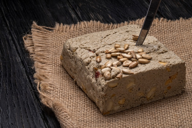 Side view of tasty halva with a knife and sunflower seeds on a sackcloth