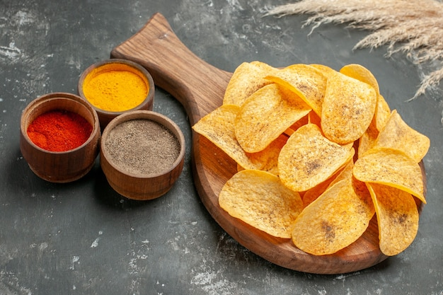 Side view of tasty potato chips spices with ketchup on gray table