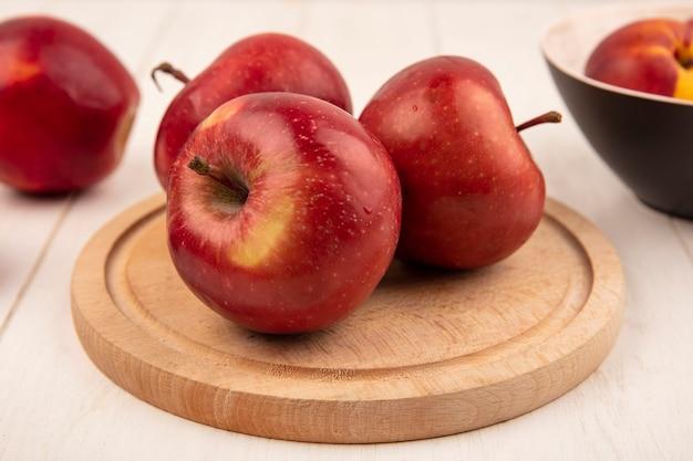 Vista laterale di gustose mele rosse su una tavola da cucina in legno su una superficie di legno bianca