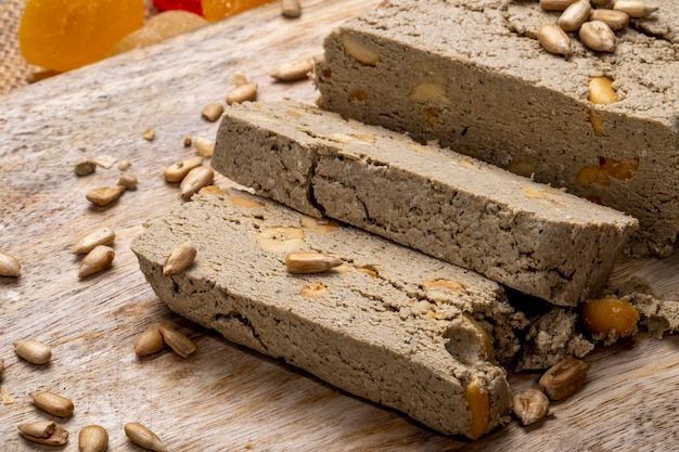 Side view of tasty slices of halva with sunflower seeds on rustic