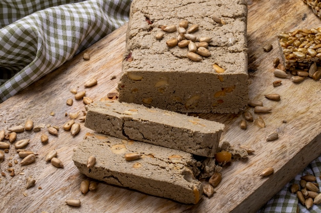 Side view of tasty slices of halva with sunflower seeds on a wooden board