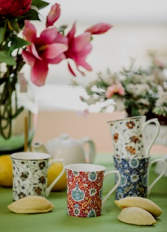 Side view of tea cups with oriental pattern and traditional azerbaijani sweetness shekerbura on floral wall