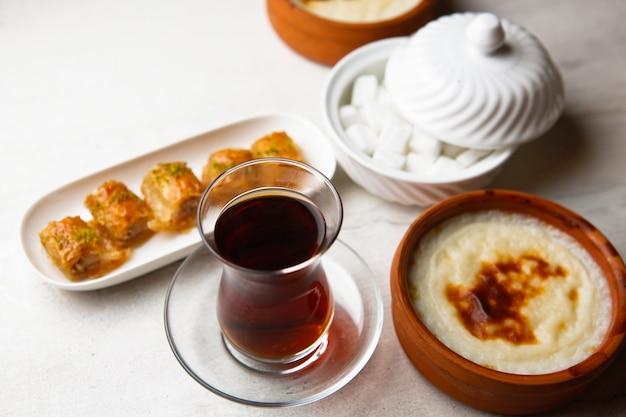 Чай в бокале армуду с пахлавой и сахаром на столе, вид сбоку