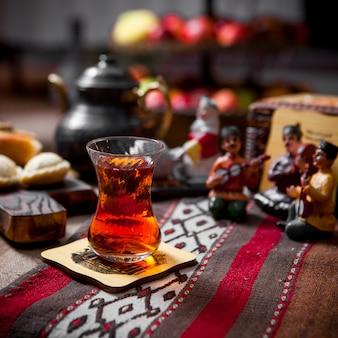 Боковой вид чайный столик со стаканом чая и статуэтками и чайником в столике в ресторане