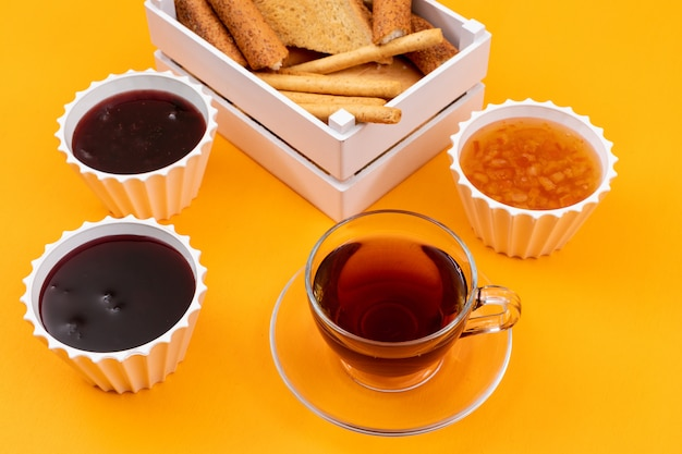 Side view of tea with jam and toasts on yellow surface horizontal