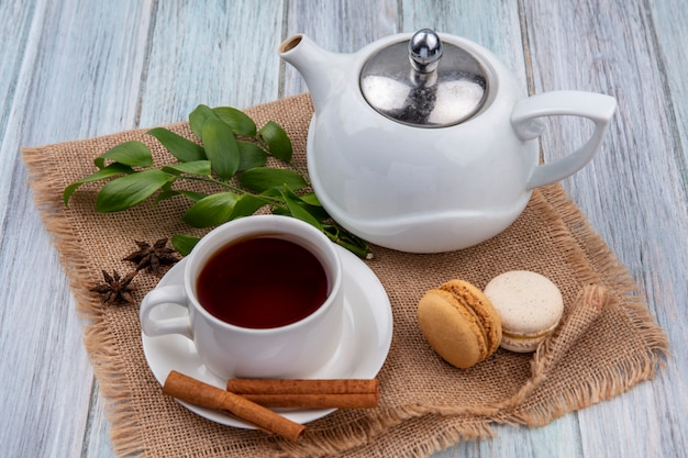 Side view of teapot with a cup of tea cinnamon and macarons on a beige napkin on a gray surface