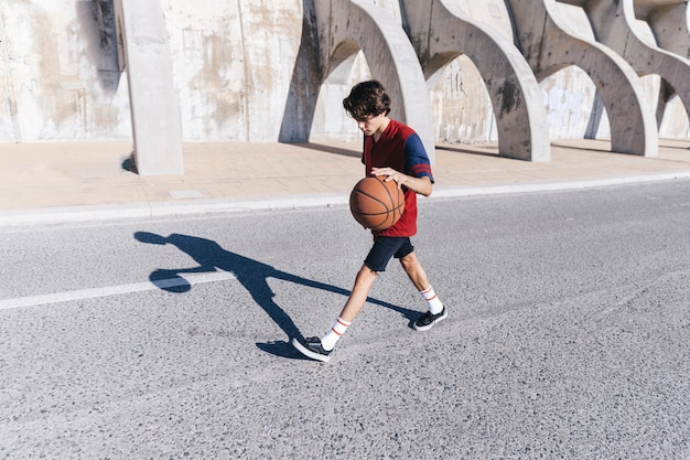 Side view of a teenage boy playing basketball near surrounding wall