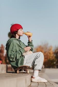 Vista laterale dell'adolescente che mangia succo il parco su skateboard