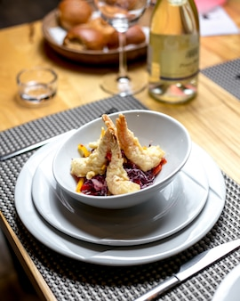 Side view of tempura shrimps with chopped red cabbage and peppers in a white bowl on the table