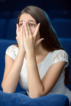 Side view of terrified young woman covering her face.
