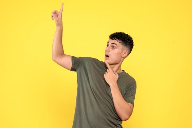 Вид сбоку: удивленный мужчина показывает вверх и держит палец за подбородок
