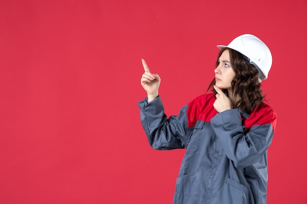 Vista laterale del premuroso costruttore femminile in uniforme con elmetto e rivolto verso l'alto su sfondo rosso isolato