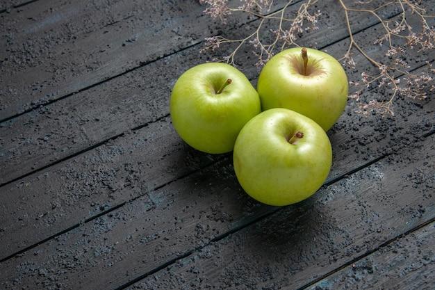 Вид сбоку три яблока зеленые яблоки на темном фоне рядом с ветвями деревьев