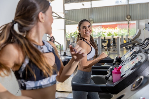Side view of three attractive sports women on running track. girls on treadmill