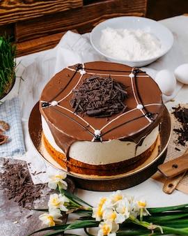 Vista laterale della torta tiramisù condita con granelli di cioccolato sul tavolo