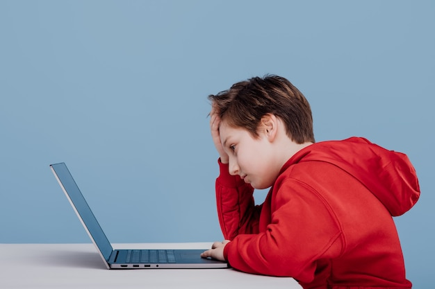 Side view tired boy with hand on forehead in front of laptop in red sweatshirt isolated blue backgro...