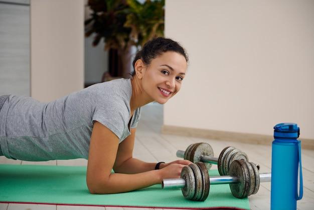 自宅のフィットネスマットで板運動をしている笑顔のスポーティな女性の側面図。鉄のダンベルとヨガマットの上に横たわっている水のボトル。