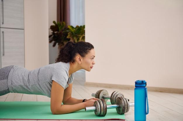 自宅のフィットネスマットで板コアエクササイズをしているスポーティな女性の側面図。ヨガマットの上に横たわっているダンベルと水のボトル。