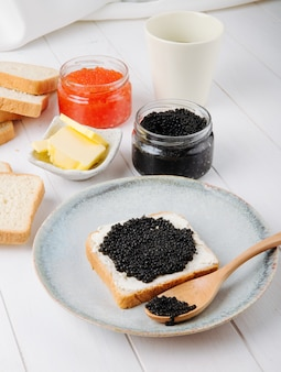 Side view toast with black caviar on a plate with a spoon and butter with a can of black and red caviar