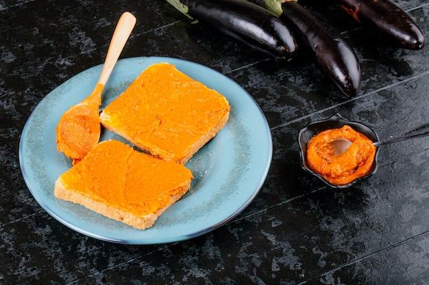Vista laterale di toast con caviale di melanzane su un piatto blu sul tavolo di legno nero
