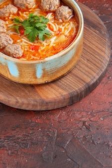 Vista laterale della zuppa di polpette di pomodoro con noodles in una ciotola marrone su sfondo scuro vista verticale