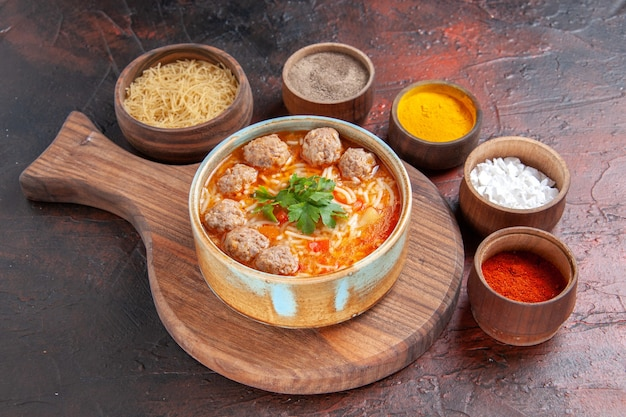 Side view of tomato meatballs soup with noodles in a brown bowl and different spices on dark background