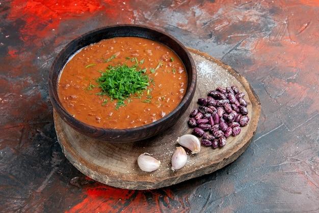 Vista laterale dell'aglio dei fagioli della zuppa di pomodoro sul tagliere di legno sulla tabella dei colori della miscela