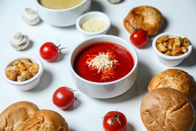 Side view tomato soup with cheese croutons tomatoes and bread