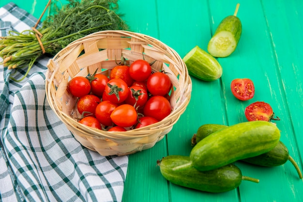 Side view of tomatoes in basket on plaid cloth and cucumber dill around on green