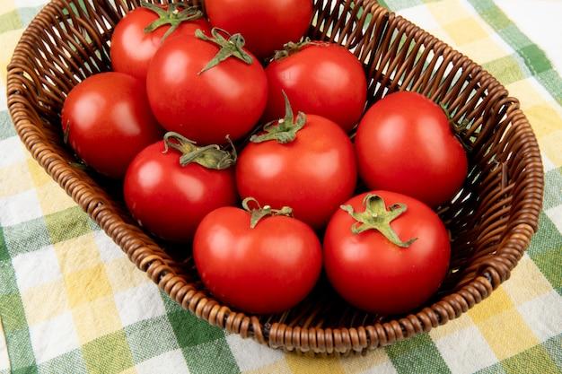 Vista laterale della merce nel carrello dei pomodori sul panno del plaid