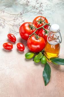 Vista laterale pomodori bottiglia di olio pomodori con pedicelli agrumi con foglie