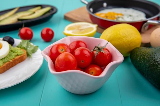Vista laterale di pomodori su una ciotola pinl con limoni uovo fritto su una padella su una tavola di cucina in legno sul blu