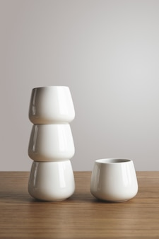 分離された厚い木製のテーブルの上のピラミッドの側面図上部の狭い形の空白の白いシンプルなコーヒーカップ