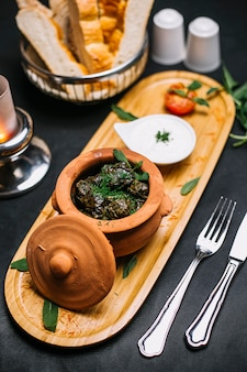 Side view a traditional azerbaijani dish dolma meat in grape leaves in a clay pot with yogurt