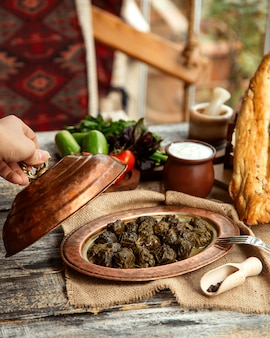 Side view a traditional azerbaijani dish meat dolma from grape leaves with yogurt and vegetables