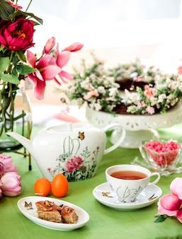 Вид сбоку на традиционную азербайджанскую сладкую пахлаву с чашкой чая с чайником и цветами на столе